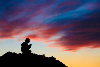 A silhouette of a young boy praying against a brilliant sunset sky.